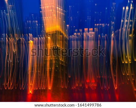 Abstract night cityscape of tilted light trails and reflections over the seawater