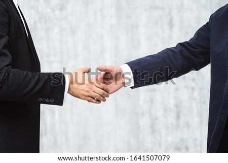 Two businessmen shake hands on a concrete wall background, insider concept, close up #1641507079
