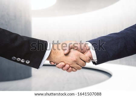 Two businessmen shake hands in the hallway, insider concept, close up #1641507088