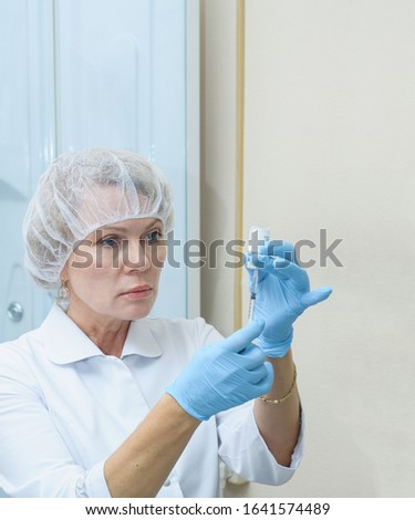 A female beautician in a medical cap and blue latex gloves holds a syringe with an injection  #1641574489