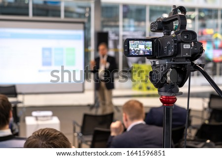 Video camera on tripod recording presentation of male coach standing on stage with display in front of audience Royalty-Free Stock Photo #1641596851