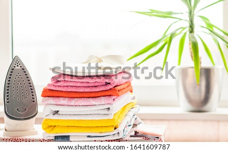ironed items and iron on ironing board #1641609787
