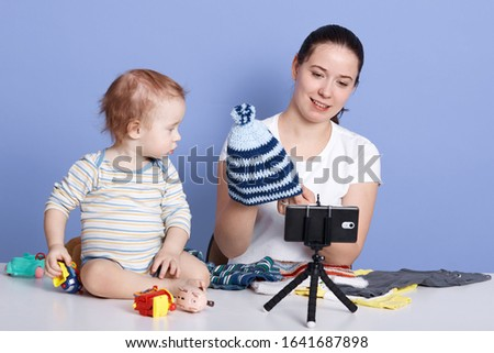 Horizontal shot of young woman holding knit cap while filming video for her channel against yblue background, sitting in front of camera with infant boy wears stripped bodysuit. Vlogging concept. #1641687898
