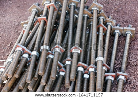 View of the group of steel anchor bolts, nuts and washers in the construction site. Anchor bolts are used to connect structural and non-structural elements to the concrete. #1641711157