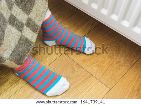 A young child warms his legs under a woolen warm blanket near a home heater in cold winter time. The concept image of the heating season at home.  #1641739141