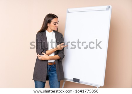 Young woman giving a presentation on white board giving a presentation on white board and pointing it #1641775858