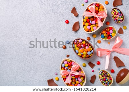 Chocolate Easter eggs and candy on concrete table, festive Easter background flat lay, copy space. Easter card with traditional treats on grey table top. Sweet Easter concept #1641828214