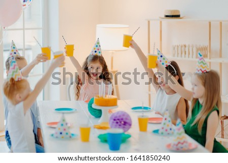 Group of cheerful preschool kids celebrate birthday together, have fun, cheer with cups of beverage, wears festive hats, eat delicious cake, sit at table in spacious room. Children and party concept #1641850240