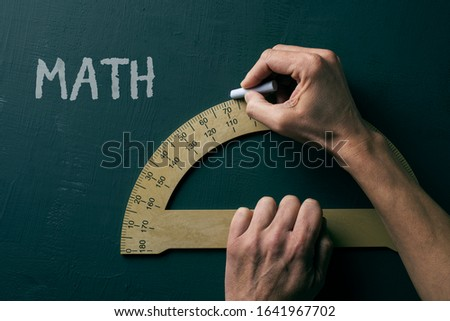 closeup of a caucasian man using a protractor and the text math, for mathematics, on a green chalkboard