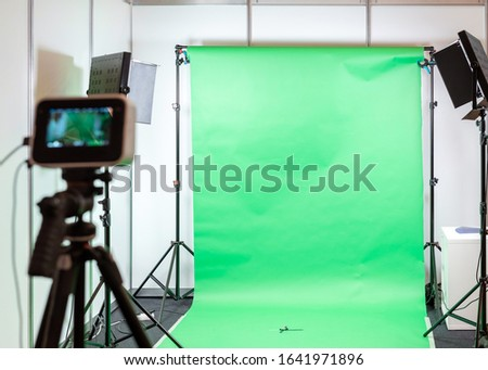 Green screen studio background. Filming or photography studio set with lights and filming equipment