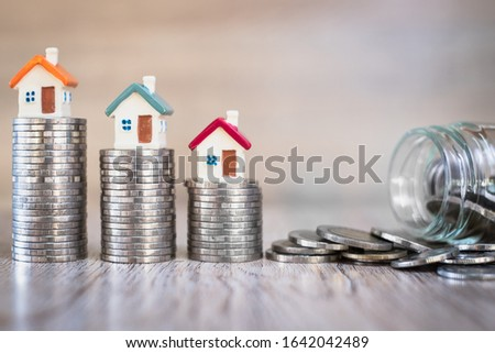 Houses on stairs, each coin glass bottles with coins placed close to each other, real estate concepts, mortgages and investments, save money or invest for future houses, space to enter text. #1642042489