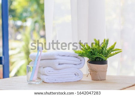 Clean handkerchief ,clean towel and Clean toothbrush put on a brown table Near the window ,morning #1642047283