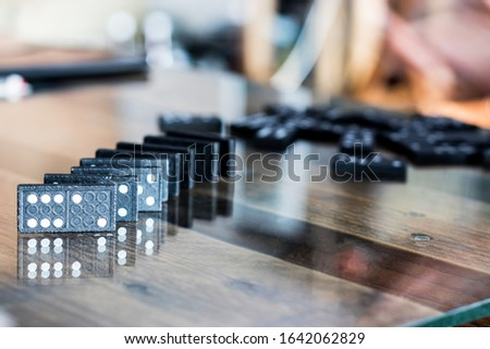 The black Domino Game, made of wood, is placed on a glass-covered wooden table on top. #1642062829