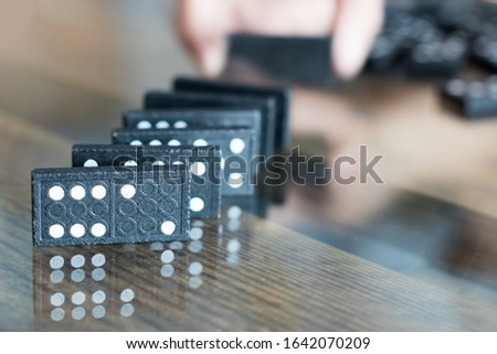 The black Domino Game, made of wood, is placed on a glass-covered wooden table on top. #1642070209