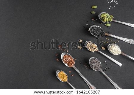 Various Seeds Assortment on black background. Set of  sesame seeds, flax seed, sunflower seeds, pumpkin seed, chia, hemp seeds in spoons, healthy food ingredients, top view, copy space. #1642105207