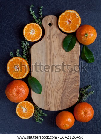 Mandarin, clementine and tangerine - Citrus fruit on the olive tree wooden board, dark slate plate background with fresh herbs -  rosemary and thyme. Creative idea with copy space , Flat lay, top view #1642126468