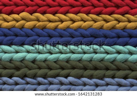 Texture of warm multi-colored woolen rug, background. Pigtail pattern, soft focus. #1642131283