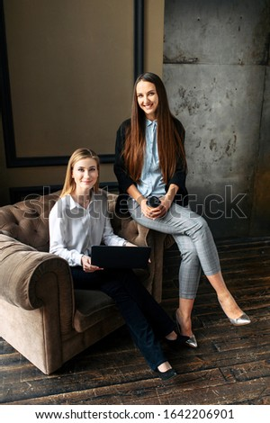 Women's team. Portrait of two girls in a smart casual. They are in casual clothes in the office with a laptop. #1642206901