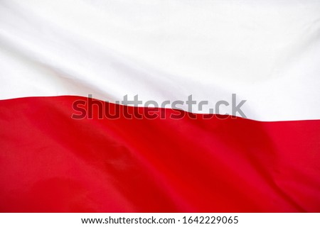 Fabric texture flag of Poland. Flag of Poland waving in the wind. Poland flag is depicted on a sports cloth fabric with many folds. Sport team banner. #1642229065