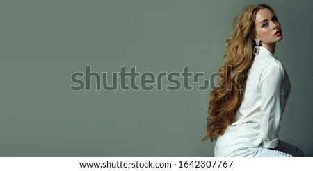 Beautiful young blue-eyed girl with luxurious long wavy red hair posing in the studio in white clothes.
