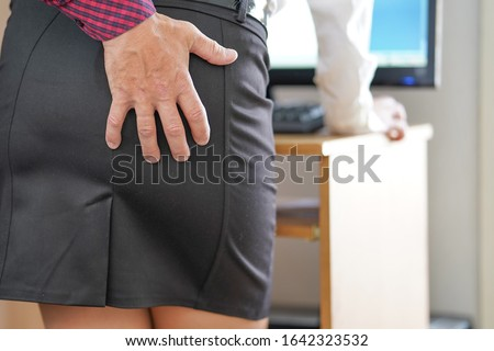 Hand Sexually Harassing Boss hugs his woman subordinate in office By Touching Her Ass. Sexual harassment at work. Manager man touches a female ass with his hand. #1642323532