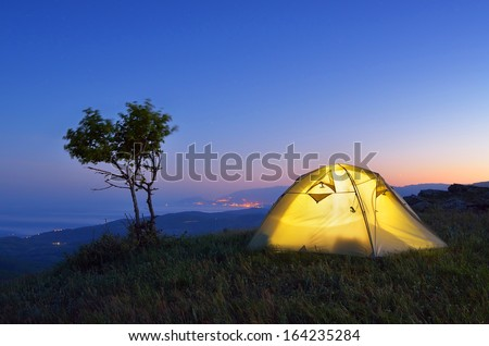 Night landscape with a tent in the mountains. The light from the lantern in a tent. Camping in the countryside. Crimea, Ukraine, Europe #164235284