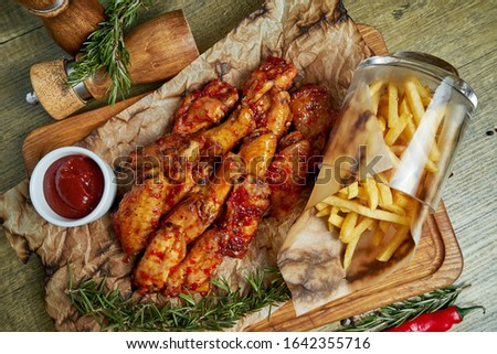 Great beer snack - spicy baked buffalo wings. BBQ wings with garnish of french fries on a wooden tray. Top view, food flat lay. Pub food