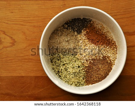 Preparation for an organic vegan, plant-based breakfast bowl with cracked oat groats, hemp seed, flax seed, ground sunflower seeds, cinnamon, and chia seeds #1642368118