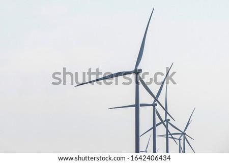 Wind farm. Wind Turbines in wind farm against sky. Energy conservation concept. Producing alternative energy #1642406434