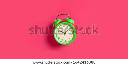 Green vintage alarm clock on bright fuchsia red background. Top view. Flat lay