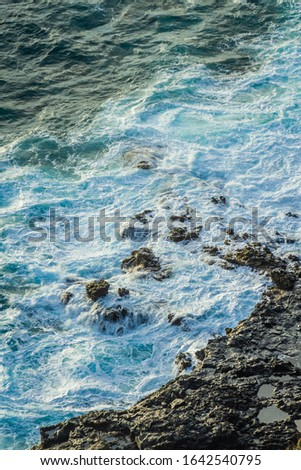Sea foam from rough ocean surf against the rocky shoreline of Hawaii. #1642540795