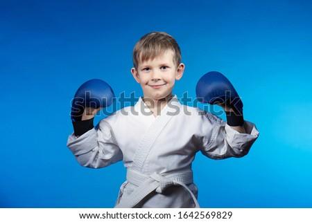 On a blue background in karategi little athlete Royalty-Free Stock Photo #1642569829