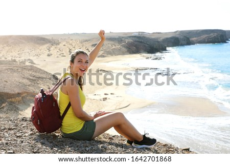 Portrait of young female hiker reaches top of mountain and celebrates with amazing landscape on the background. Happy success backpacker girl celebrating outdoor raising her fist up in exultation. #1642701868