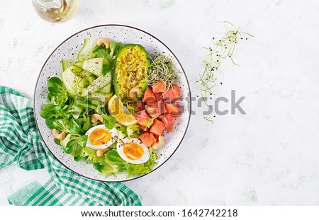 Ketogenic diet breakfast. Salt salmon salad with greens, cucumbers, eggs and avocado. Keto/paleo lunch. Top view, overhead Royalty-Free Stock Photo #1642742218