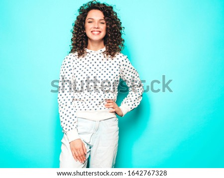 Portrait of beautiful smiling model with afro curls hairstyle dressed in summer hipster clothes.Sexy carefree girl posing near blue wall.Trendy funny and positive woman in white hoodie