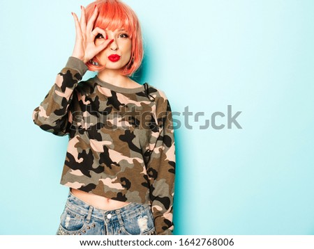 Portrait of young beautiful hipster bad girl in trendy red summer clothes and earring in her nose.Sexy carefree smiling woman posing in studio in pink wig.Model covers her eye and shows ok sign #1642768006