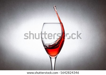 Glass with splashes, drops of red wine on a white background. Freezing liquids in motion #1642824346