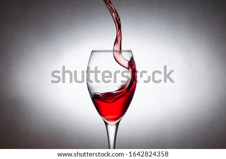 Glass with splashes, drops of red wine on a white background. Freezing liquids in motion #1642824358