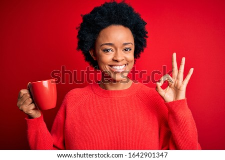 African American afro woman with curly hair drinking cup of coffee over red background doing ok sign with fingers, excellent symbol #1642901347