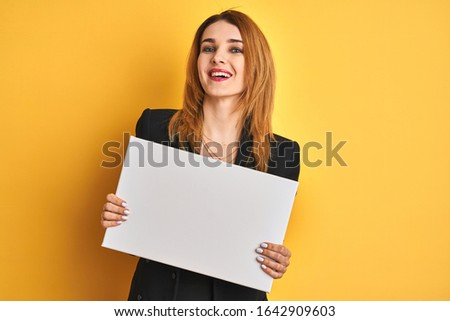 Redhead business caucasian woman holding banner over yellow isolated background with a happy face standing and smiling with a confident smile showing teeth