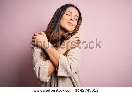 Young beautiful brunette woman wearing casual sweater standing over pink background Hugging oneself happy and positive, smiling confident. Self love and self care Royalty-Free Stock Photo #1642943812