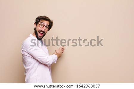 young cool bearded man expressing a concept against flat wall #1642968037