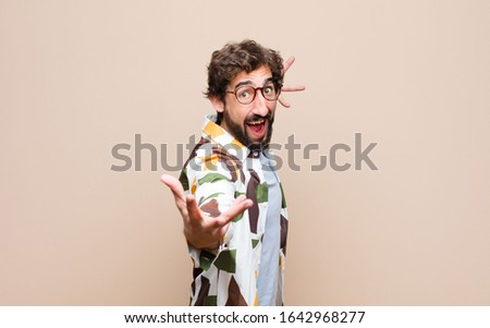 young cool bearded man expressing a concept against flat wall #1642968277