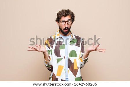 young cool bearded man expressing a concept against flat wall #1642968286