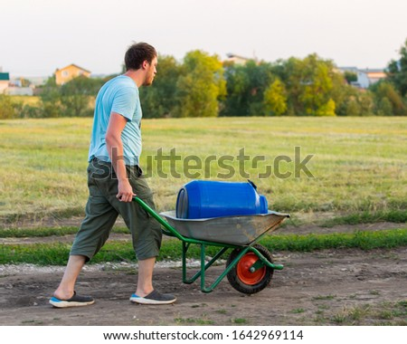 A farmer carries a blue barrel in a metal trolley along a country road. Worker carries a cart, village life, a farmer carries water in a plastic barrel #1642969114