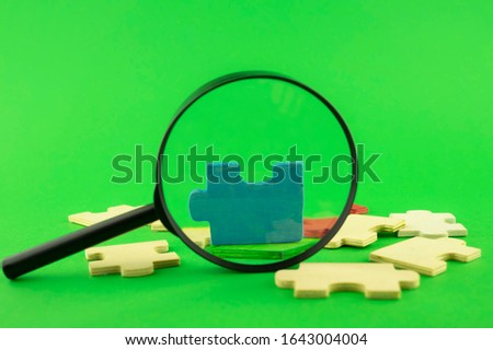 Colorful jigsaw puzzle pieces with magnifying glass focused on a single blue corner piece in a conceptual image over green for search, investigation and problem solving #1643004004