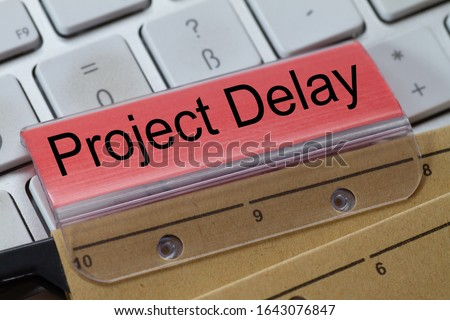 hanging file on a keyboard with red label written: Projekt Delay Royalty-Free Stock Photo #1643076847