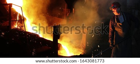 Liquid metal in the foundry, melting iron in furnace, steel mill. Worker with goggles and helmet controlling iron smelting in furnaces, applying heat to ore in order to extract a base metal #1643081773