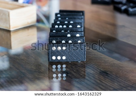 The black Domino Game, made of wood, is placed on a glass-covered wooden table on top. #1643162329