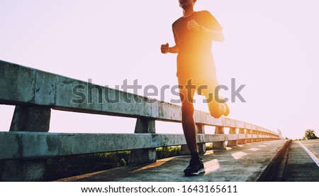 Athlete runner feet running on road, Jogging at outdoors. Man running for exercise.Sports and healthy lifestyle concept. Royalty-Free Stock Photo #1643165611